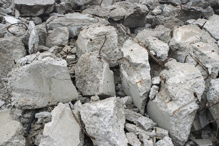 Fragments of concrete slabs in the form of large gray stones with protruding reinforcement. Background. 版權商用圖片