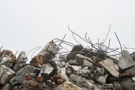 Les barres d'armature dépassant des tas de gravats de brique, de pierre et de gravats de béton contre le ciel dans une brume. Banque d'images