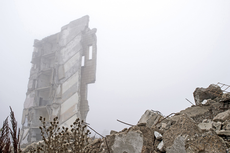 The remains of concrete fragments of gray stones on the background of the destroyed building in a foggy haze. The impact of the destruction. Background. Stock Photo