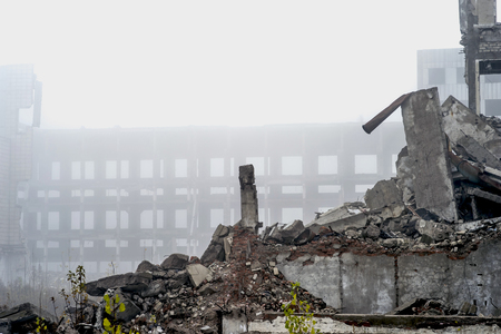 The remains of a large destroyed building with concrete pilings and scattered bricks with rebar against the frame of a large building in the fog. Copy space. Stock Photo
