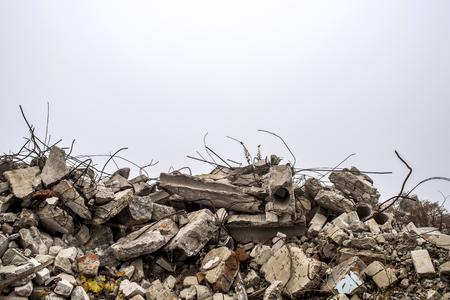 Il tondo per cemento armato che spunta da cumuli di macerie di mattoni, pietre e macerie di cemento contro il cielo in una foschia. Resti dell'edificio distrutto. Copia spazio.