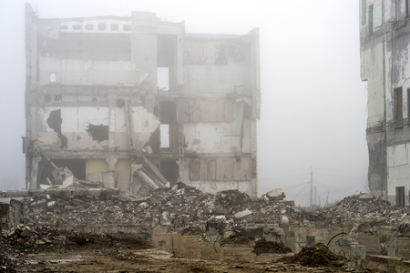 The remains of the destroyed Foundation of the building in the form of piles and rubble from a pile of concrete fragments of stones on the background of the destroyed structure in a foggy haze.