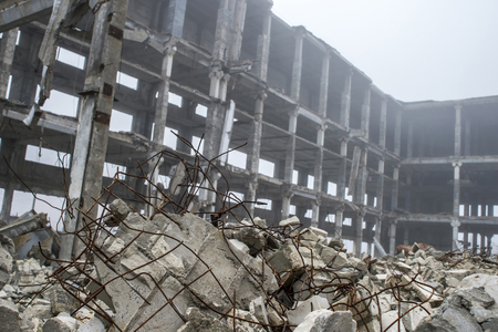 A pile of gray concrete stones with protruding reinforcement on the background of the frame of a large destroyed building in a foggy haze. Background.