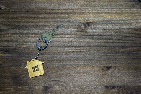 Symbol of a bamboo house with a metal key on a brown vintage wooden background. Lighting gradient. The concept of selling real estate with the transfer of ownership. Stock Photo