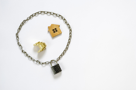 Imitation of a house made of wood with yellow coins in a perimeter limited by a chain on the lock. Stock fotó
