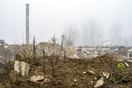 The remains of a large concrete building in the misty haze in the form of fragments of piles and piles of stones. The impact of the destruction. Background.