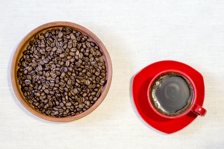 Red mug of freshly brewed coffee with roasted beans in a ceramic clay pan on linen canvas. Top view, flat lay. Фото со стока