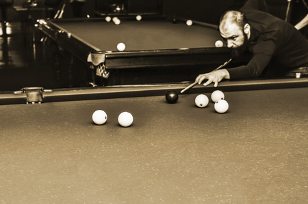 Billiards player in the club Premier, Russia, Kursk region, Zheleznogorsk, December 2017. The sharpness on the front of the white balls.