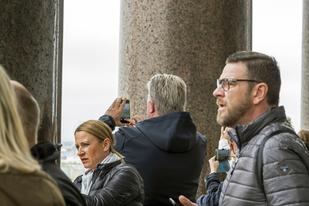 Man tourist European appearance photographs on smartphone neighborhood of St. Petersburg with the colonnade of St. Isaacs Cathedral surrounded by tourists, Russia, St. Petersburg, September 2018.