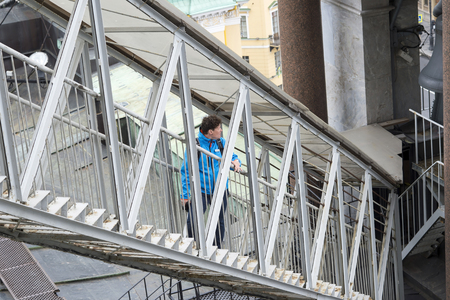 Middle aged woman climbs a metal staircase to the colonnade of St. Isaacs Cathedral in St. Petersburg, Russia, September, 2018. The view from the top.