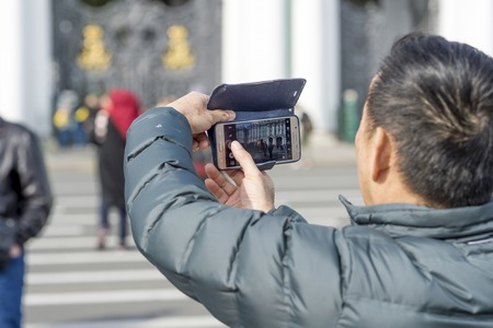 A man tourist of Asian appearance photographs on a smartphone the Hermitage building on the Palace square of St. Petersburg, Russia, September 2018. The view from the back. Redakční