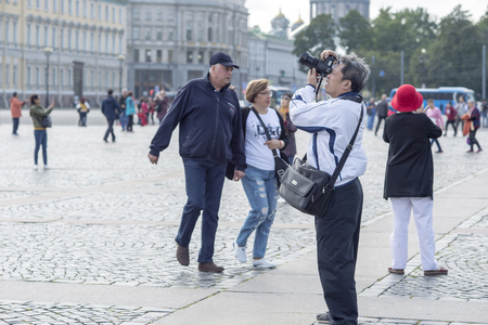 A male tourist of Asian surrounded by other tourists appearance in a white jacket photographs the sights on the Palace square of St. Petersburg, Russia, September 2018. Side view. Redakční