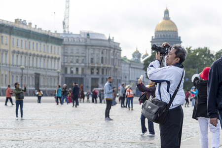A male tourist of Asian appearance in a white jacket photographs the sights on the Palace square of St. Petersburg, Russia, September 2018. Side view.