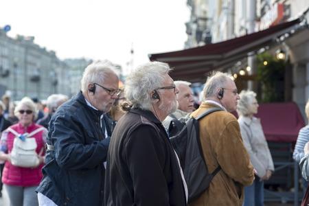 Elderly men of European appearance on a tour in headphones radio guide on Nevsky Prospekt St. Petersburg, Russia, September 2018. Side view. Redakční