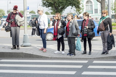 Group of female tourists waiting at the crosswalk in the area of Palace square of St. Petersburg, Russia, September, 2018.