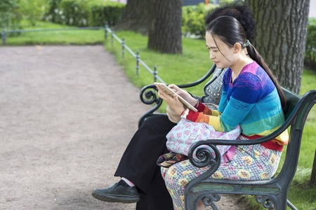 A girl from Asia sits on a bench with a companion and looks at the tablet in the Park at the entrance to the Hermitage Museum of St. Petersburg, Russia, September, 2018. Copy space. Redakční