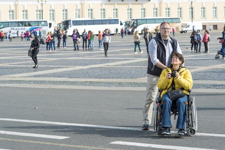 Caucasian man carries a woman enthusiastically photographing on camera in a wheelchair on a trip to the Palace square of St. Petersburg, Russia, September, 2018.