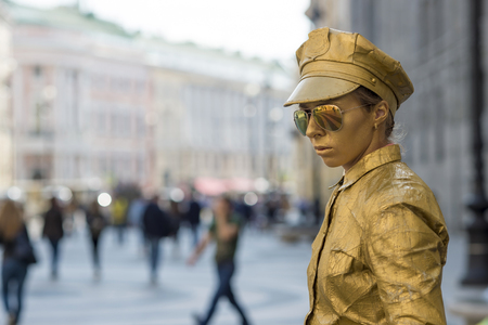 The girl is completely in gold paint and retro police uniform near the Palace square of St. Petersburg, Russia, September, 2018. The concept of entertainment for tourists, animation.