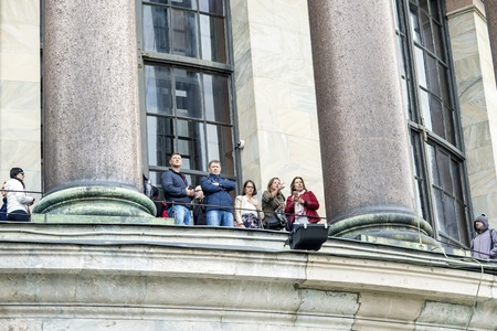 A group of tourists of European appearance overlook the colonnade of St. Isaacs Cathedral, St. Petersburg, Russia, September, 2018.