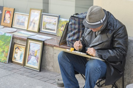 An elderly man artist in a leather coat and hat, with his head down, draws a picture against the background of his own works on Nevsky Prospect in St. Petersburg, Russia, September, 2018.