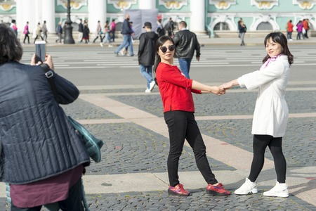 Young women of Asian appearance are photographed on Palace square against the background of the Hermitage in St. Petersburg, Russia, September, 2018.