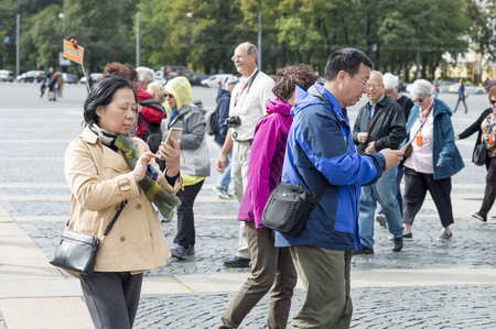 Oriental tourists man and woman go on a mobile gps route on the background of an organized group of other tourists of St. Petersburg, Russia, September, 2018.