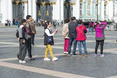 Group of Oriental tourists of Asian appearance on the Palace square of St. Petersburg on the background of the Hermitage, Russia, September 2018. Side and back view.