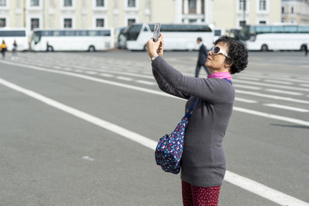 Woman tourist Eastern appearance photographs on the phone attractions on the background of white tourist buses on the Palace square of St. Petersburg, Russia, September, 2018.