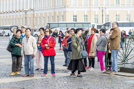 Group of Oriental tourists of Asian appearance on the Palace square of St. Petersburg on the background of white tourist buses, Russia, September 2018. Front view.