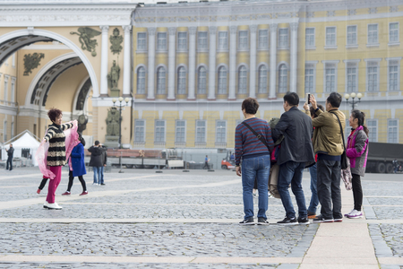 A woman tourist of Eastern appearance posing for a group of compatriots on the Palace square of St. Petersburg, Russia, September, 2018. Sharpness on a group of people.