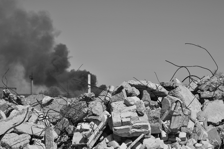 A pile of concrete rubble with protruding rebar on the background of thick black smoke in the sky. Background. The concept of the consequences of human activities. Black and white image.