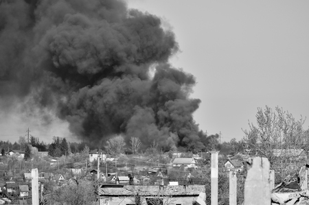 A pile of concrete rubble with protruding rebar on the background of thick black smoke in the blue sky. Background. The concept of the consequences of human activities. Black and white image.
