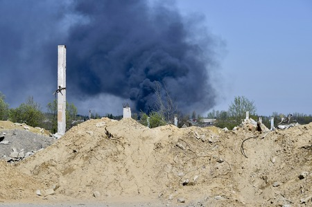 A pile of concrete rubble with protruding rebar on the background of thick black smoke in the blue sky. Background. The concept of the consequences of human activities.
