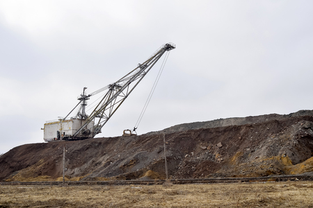 Large walking excavator in anticipation of rolling stock transporting overburden for storage in dumps. Industrial landscape after the destruction of nature by man.