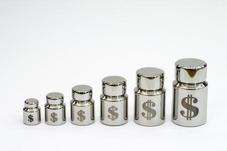 Gráfico de pesos metálicos con grabado láser de símbolos del dólar sobre un fondo gris claro.
