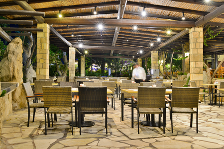 Cafe at night at the Coral Beach Hotel Resort Cyprus Paphos in June 2017 in Cyprus. Shooting on a long exposure with a tripod, blurred waiter carries Cutlery for Breakfast. Redakční