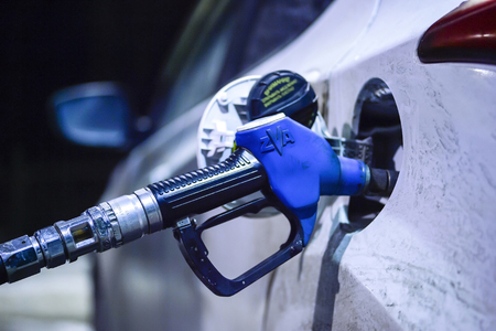 Fuelling nozzle inserted into the tank of white car at the petrol station TNK on the track Borisoglebsk - Saratov, December 2017.