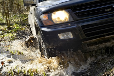 SUV close-up front of it passes over rough terrain, through a puddle on a dirty road. Sharpness in the middle field.