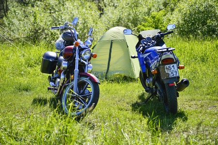 Motorcycles red and blue on green grass on the background of green tourist tent at the festival Meeting of summer Russia, Kursk region, Zheleznogorsk, may 2018. Redakční
