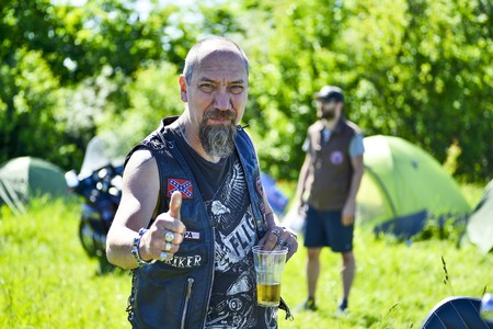 Man biker holding a glass of beer at the festival Meeting of summer Russia, Kursk region, Zheleznogorsk, may 2018. The concept of life on wheels.