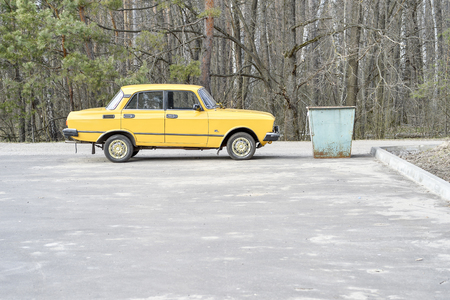 Old yellow car brand Moskvich AZLK 2140 parked near the garbage can in the Parking lot of the sanatorium Miner Russia, Kursk region, Zheleznogorsk, April, 2019. The concept of garbage that drives.