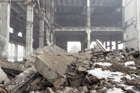 The destroyed big concrete building in a foggy haze with the remains of snow. The remains of the frame of gray concrete piles, slabs and debris of the building structure. Background. Stock Photo