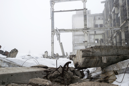 Destroyed large concrete building in a foggy haze with the remains of snow. The frame of the building structure with huge piles lying in the foreground. Background.