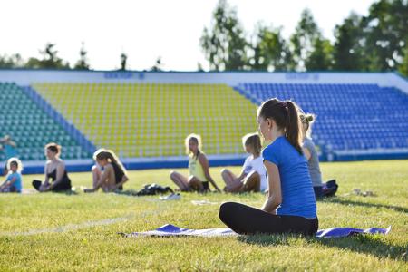 A young woman performs gymnastics yoga exercises at the city stadium, Russia, Kursk region, Zheleznogorsk, June 2018. Redakční