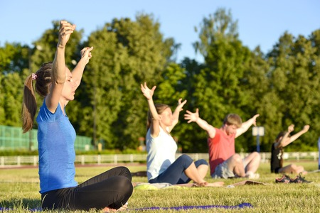 Yoga exercises class breathing technique group of people at the city stadium Russia, Kursk region, Zheleznogorsk, June 2018. A young woman in the foreground doing the exercise. Redakční