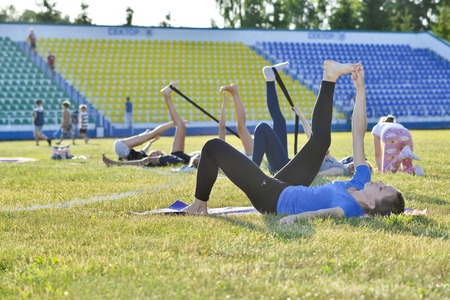 A young woman performs gymnastics yoga exercises at the city stadium, Russia, Kursk region, Zheleznogorsk, June 2018. Редакционное