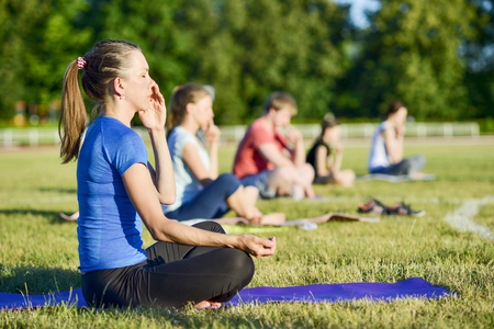 Young woman in a blue shirt doing yoga in a group at the city stadium, Russia, Kursk region, Zheleznogorsk, June 2018. The concept of a healthy lifestyle.