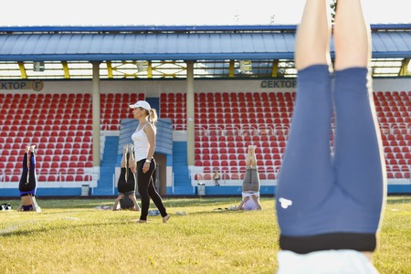 Woman yoga coach shows exercises at the city stadium, Russia, Kursk region, Zheleznogorsk, June 2018.