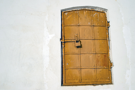 Antique iron-bound window with a latch. The concept of the template is hidden or falsified secrets of history, the true facts and knowledge. Place for text on the white wall.