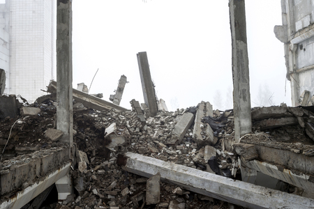 The destroyed big concrete building in a foggy haze. The remains of the frame of gray concrete piles and debris of the building structure. Background. Standard-Bild